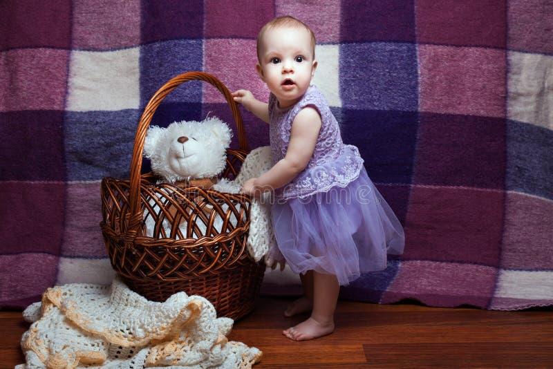 La muchacha se coloca cerca de la cesta foto de archivo libre de regalías