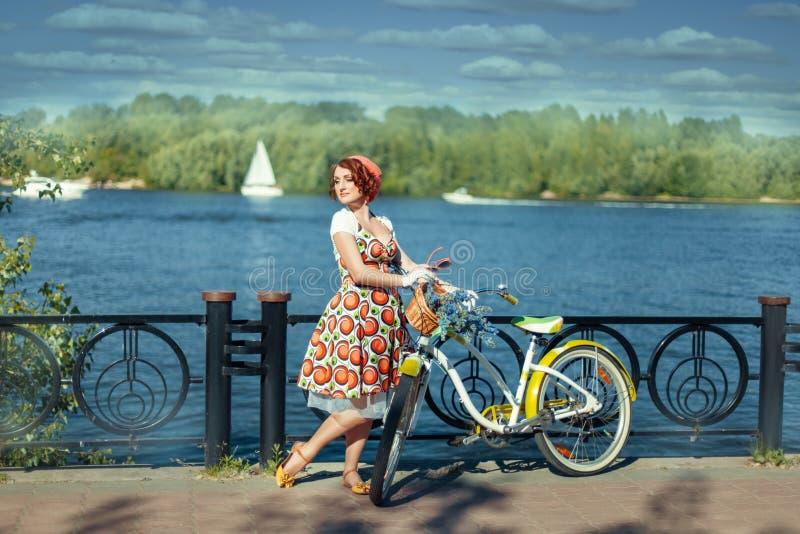 La muchacha se coloca cerca de una bici en la orilla imagenes de archivo