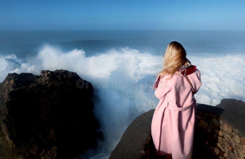 La muchacha se coloca cerca del agua Tormenta en el mar Océano tempestuoso Rompeolas de piedra imágenes de archivo libres de regalías