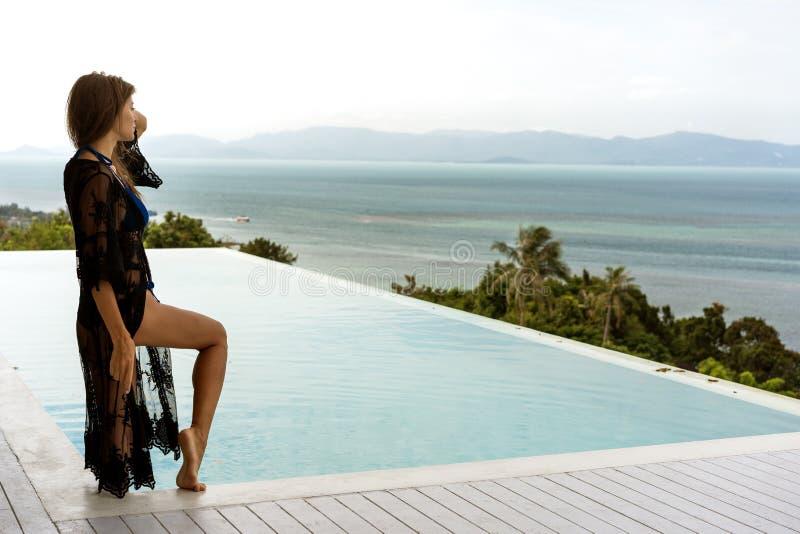 La muchacha se coloca en la costa que pasa por alto las montañas cerca de la piscina fotos de archivo libres de regalías