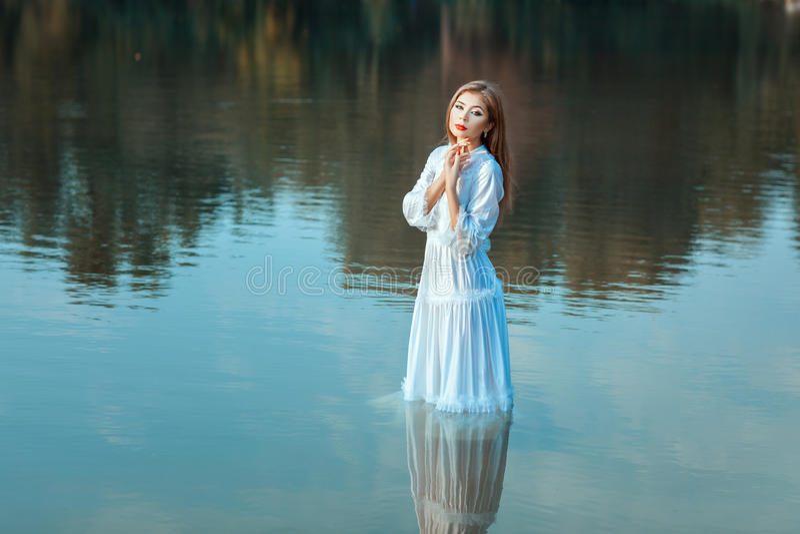 La muchacha se coloca en el agua imagen de archivo