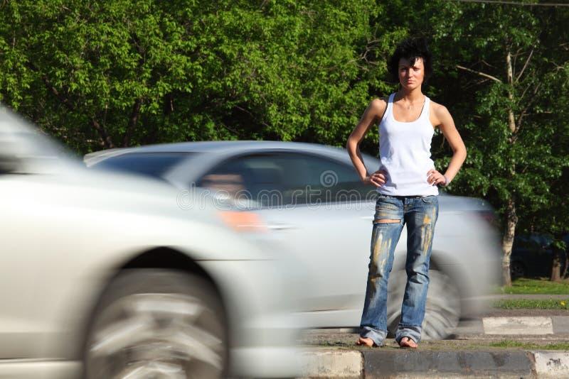 La muchacha se coloca en el camino entre los coches imagen de archivo libre de regalías
