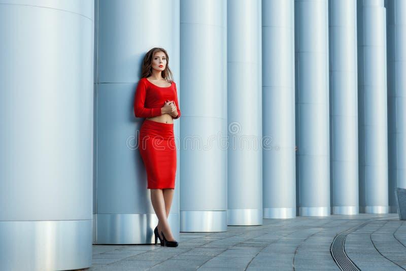 La muchacha se coloca en la columnata del fondo Fotografía de la manera foto de archivo