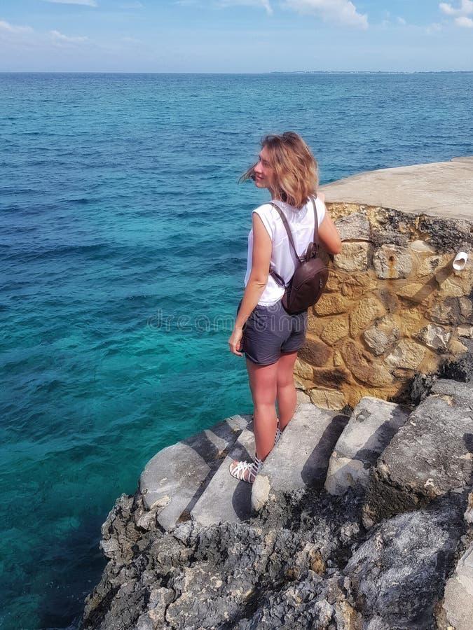 La muchacha se coloca en rocas, rocas y miradas en el mar del Caribe foto de archivo