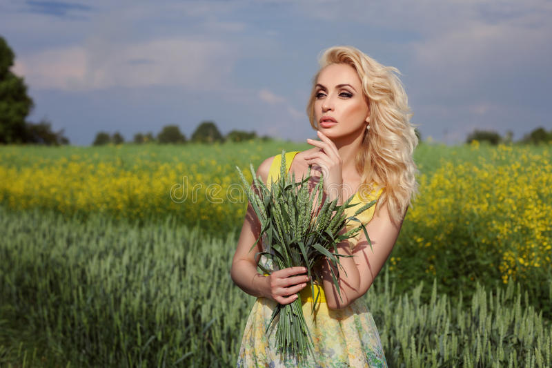 La muchacha se coloca en un campo En el fondo, flores amarillas imagen de archivo libre de regalías