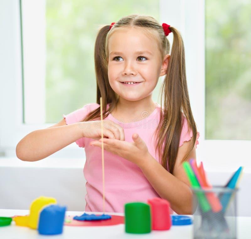 La muchacha se está divirtiendo mientras que juega con plasticine foto de archivo libre de regalías