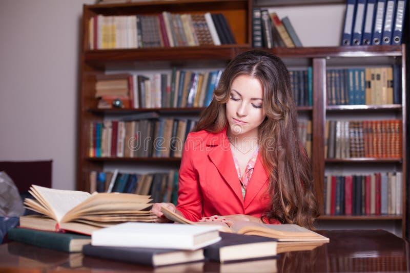 La muchacha se está preparando para el examen en la biblioteca imagen de archivo