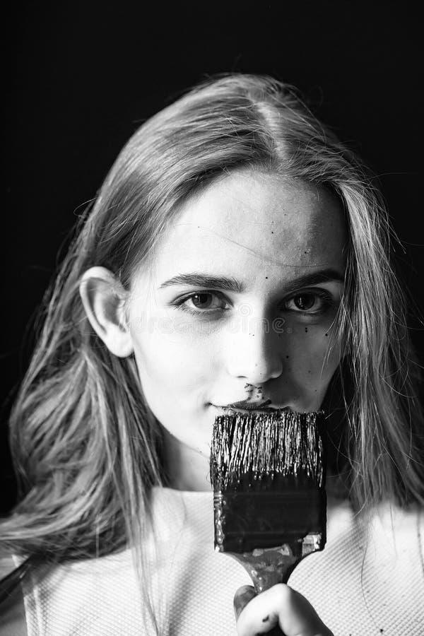 La muchacha se está preparando para reparar el apartamento el constructor bonito de la muchacha, pintor con la brocha negra, tien foto de archivo libre de regalías