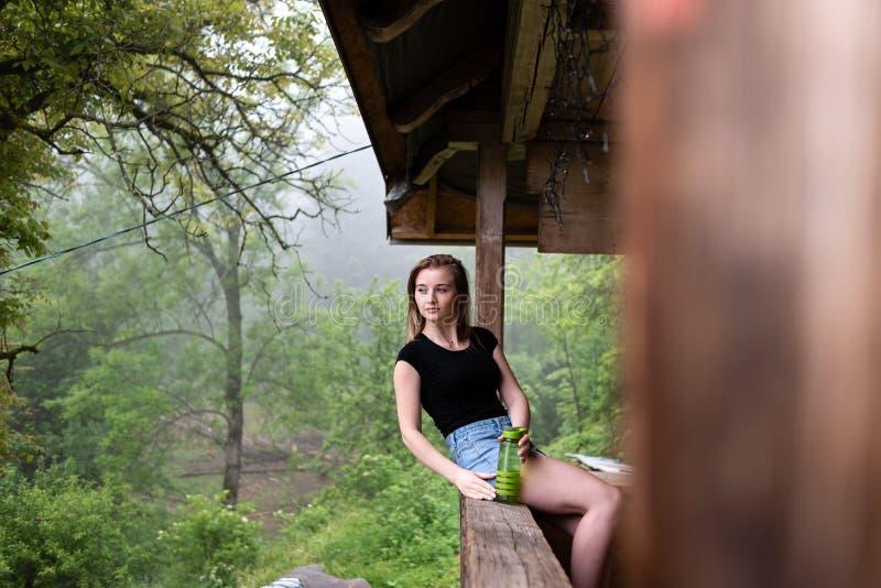 La muchacha se está sentando en la cerca fotografía de archivo libre de regalías