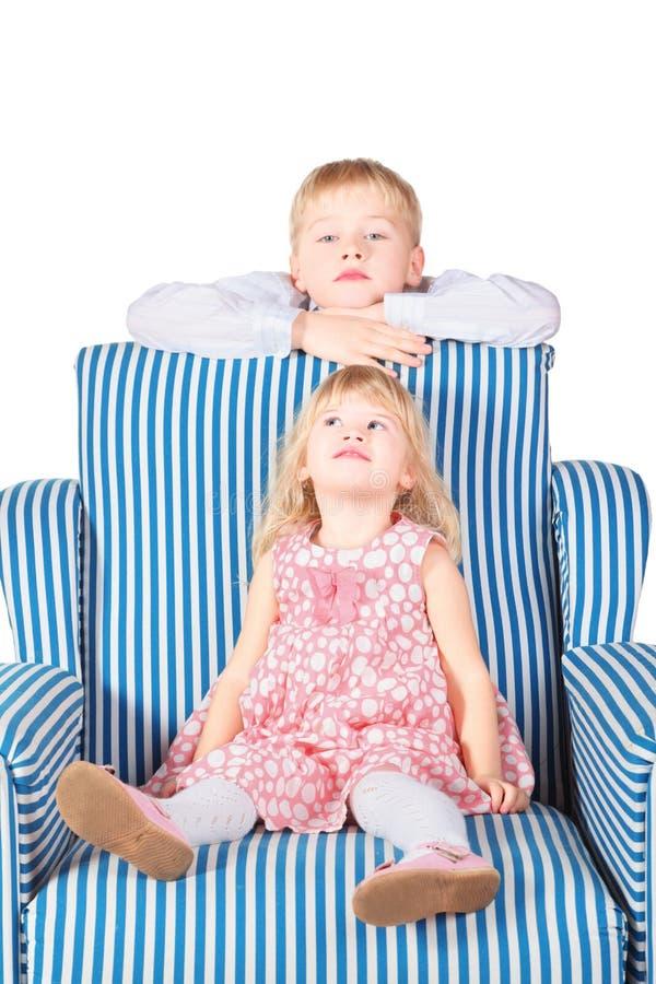 La muchacha se está sentando en silla. el hermano está detrás fotografía de archivo