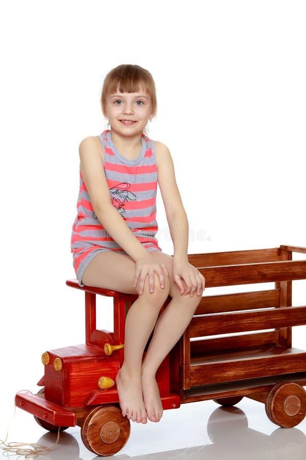 La muchacha se está sentando en un coche de madera del juguete grande imagen de archivo