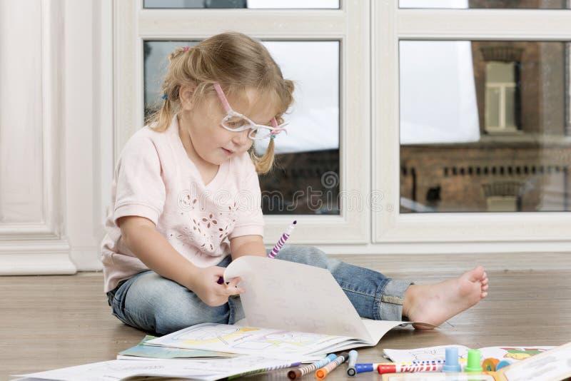 La muchacha se está sentando en un piso y un dibujo fotos de archivo libres de regalías