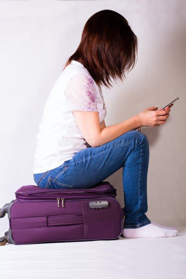 La muchacha se está sentando en una maleta imágenes de archivo libres de regalías