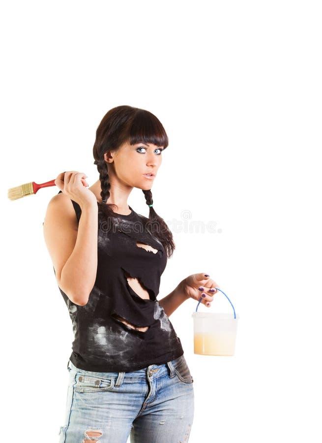 La muchacha se prepara para pintar una pared imagen de archivo