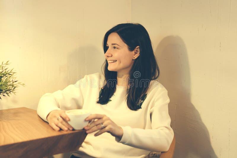La muchacha se ríe de una tabla del café fotos de archivo libres de regalías
