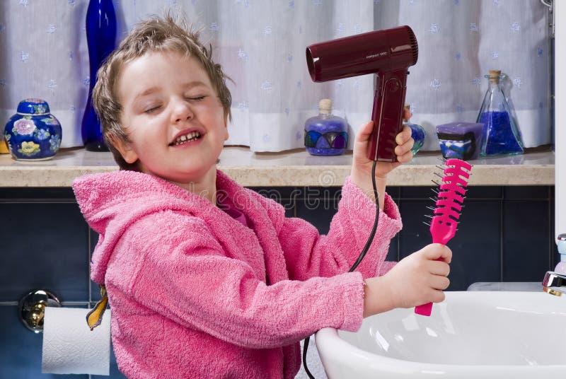 La muchacha se seca el pelo con el secador de pelo imagen de archivo libre de regalías