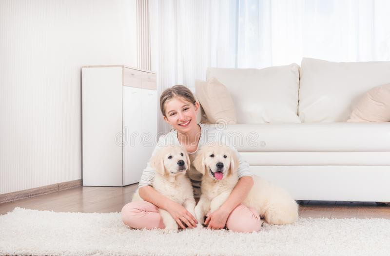 La muchacha se sienta abrazando perritos del perro perdiguero fotografía de archivo