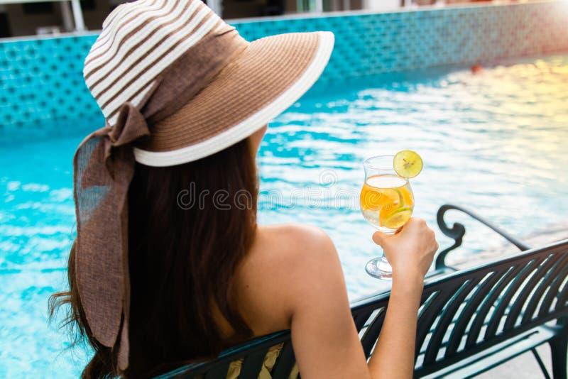 La muchacha se sienta al lado de la mano de la encuesta del swimmimg que sostiene el zumo de naranja en la mañana foto de archivo