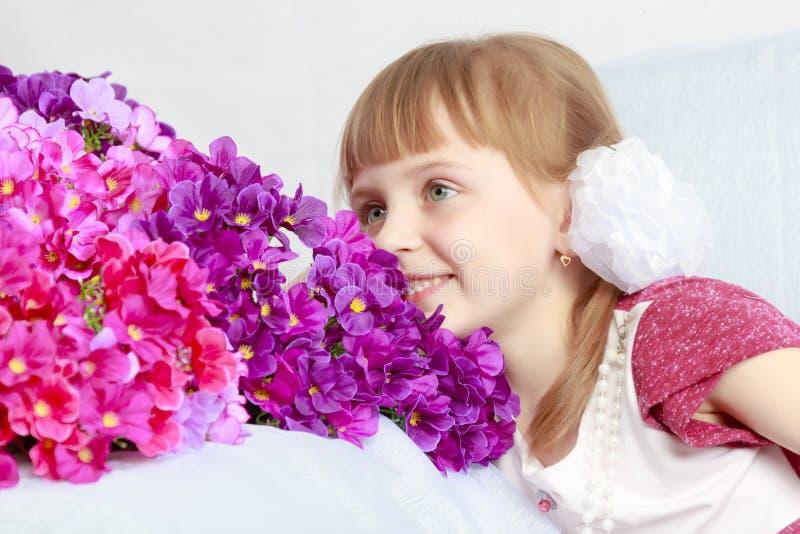 La muchacha se sienta al lado de un ramo de flores foto de archivo libre de regalías