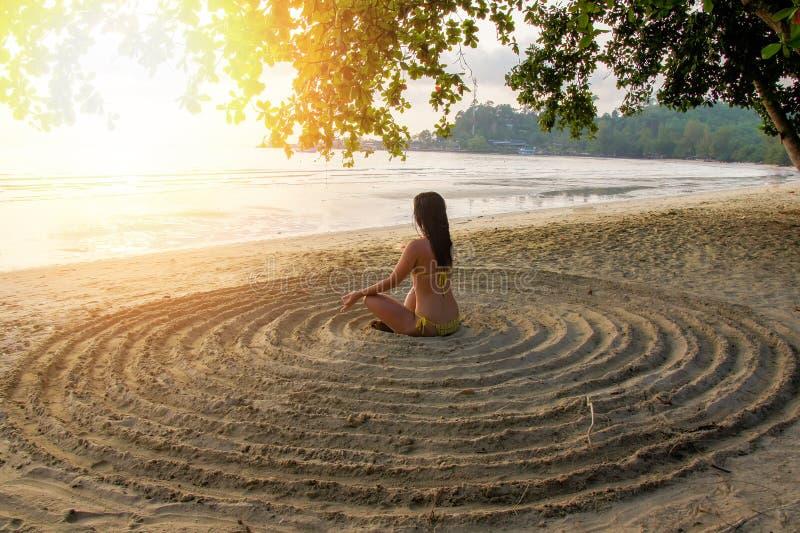La muchacha se sienta c?modamente en la playa arenosa en el centro de un c?rculo improvisado y medita foto de archivo