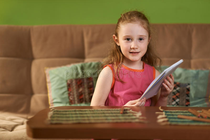 La muchacha se sienta con el cuaderno a disposición imagen de archivo libre de regalías