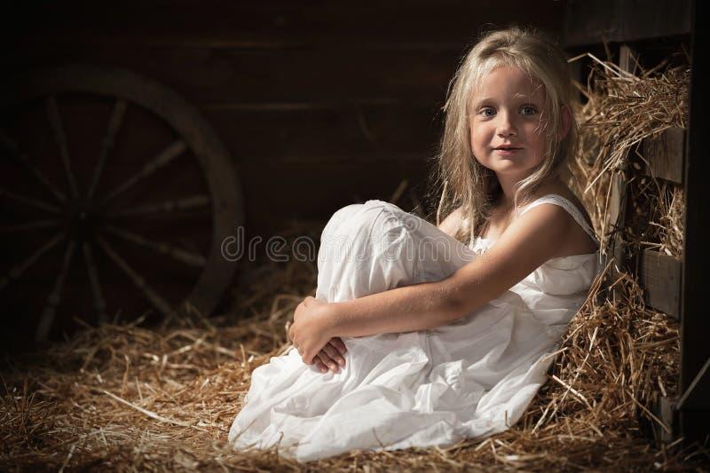 La muchacha se sienta en el heno en el granero imagenes de archivo