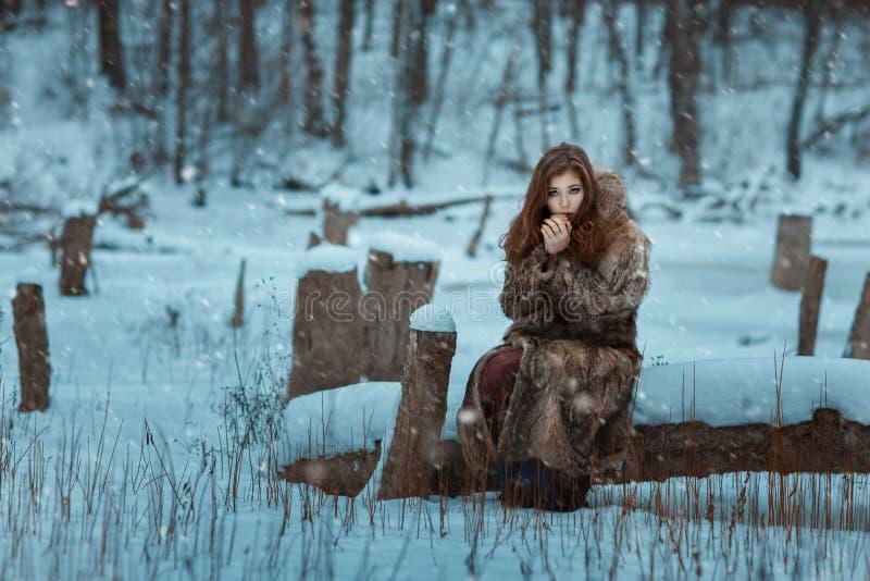 La muchacha se sienta en el invierno y calienta las manos fotografía de archivo libre de regalías