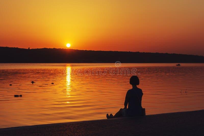 La muchacha se sienta en la orilla de una piscina en la ciudad y mira la puesta del sol imagen de archivo
