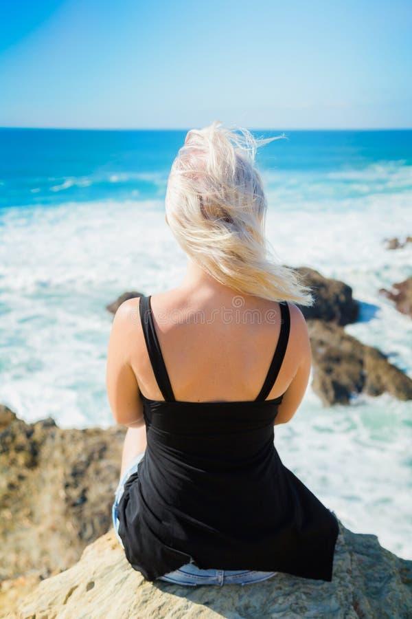 La muchacha se sienta en un acantilado sobre el océano imagenes de archivo
