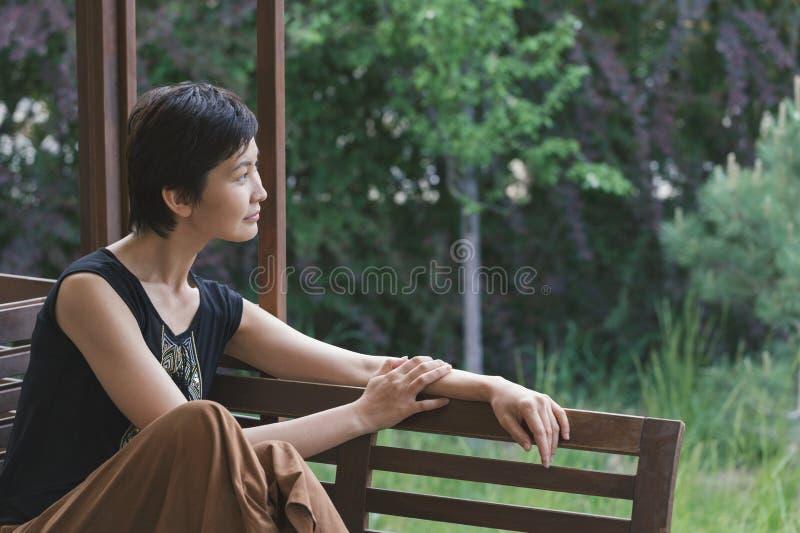 La muchacha se sienta en un banco y mira cuidadosamente en la distancia Sueños de la mujer Relájese foto de archivo