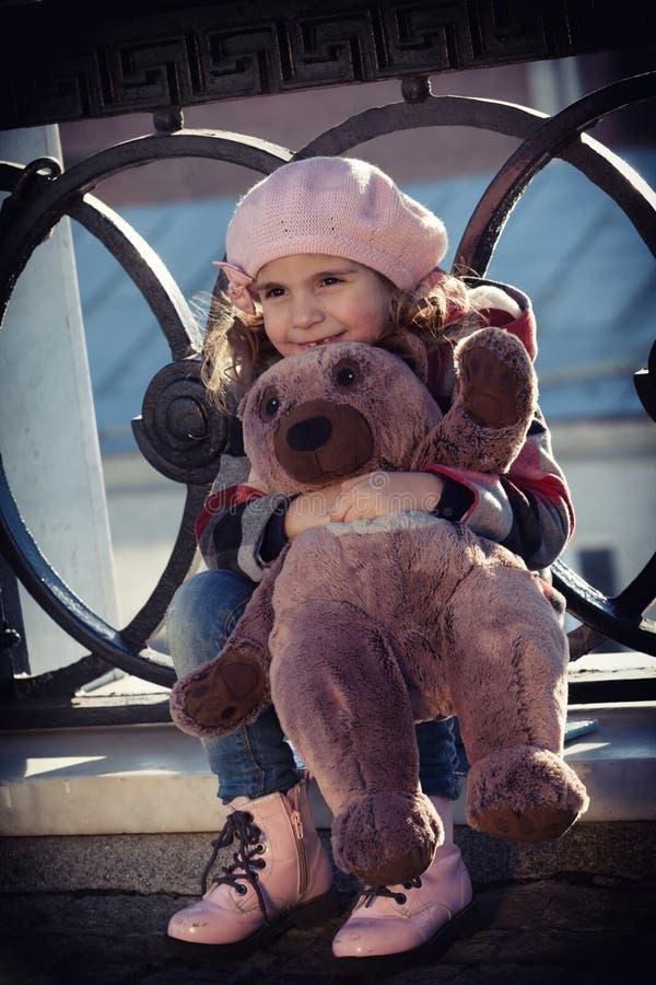 La muchacha se sienta en un cercado del arrabio del puente fotografía de archivo libre de regalías