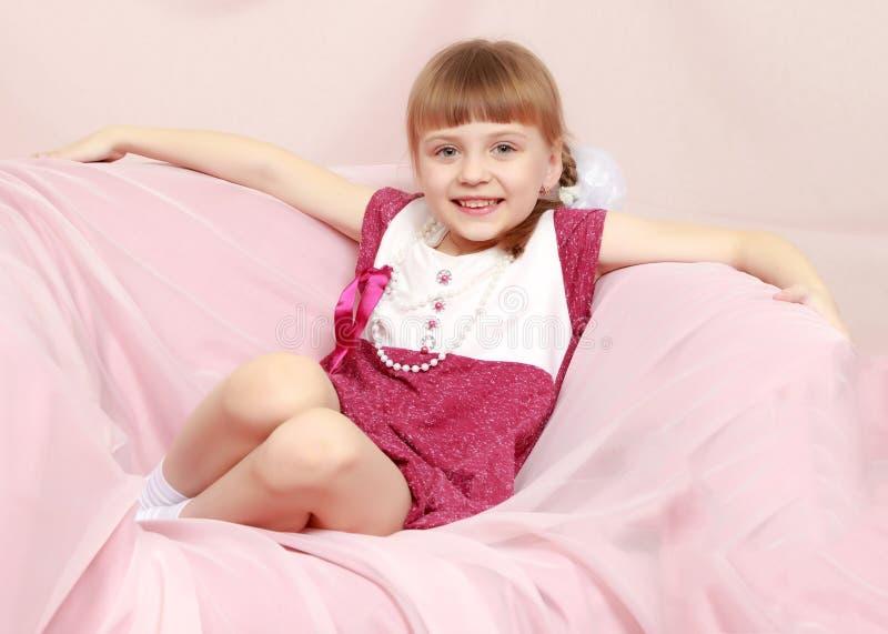 La muchacha se sienta en un sofá rosado imagen de archivo