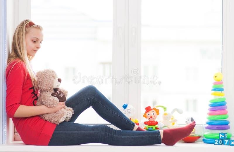 La muchacha se sienta en un travesaño de la ventana con los juguetes imagen de archivo libre de regalías