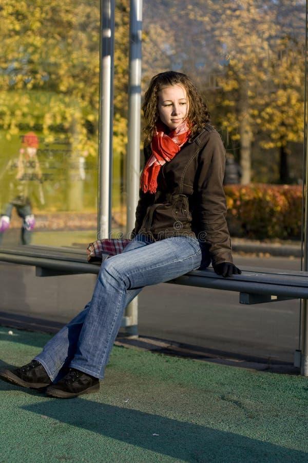 La muchacha se sienta en una parada de omnibus imagen de archivo libre de regalías