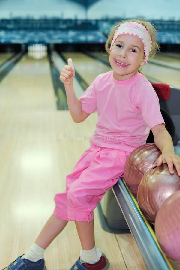 La muchacha se sienta y manosea con los dedos para arriba en club del bowling fotos de archivo