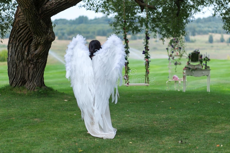 La muchacha se vistió como un ángel en el jardín de Eden imagenes de archivo