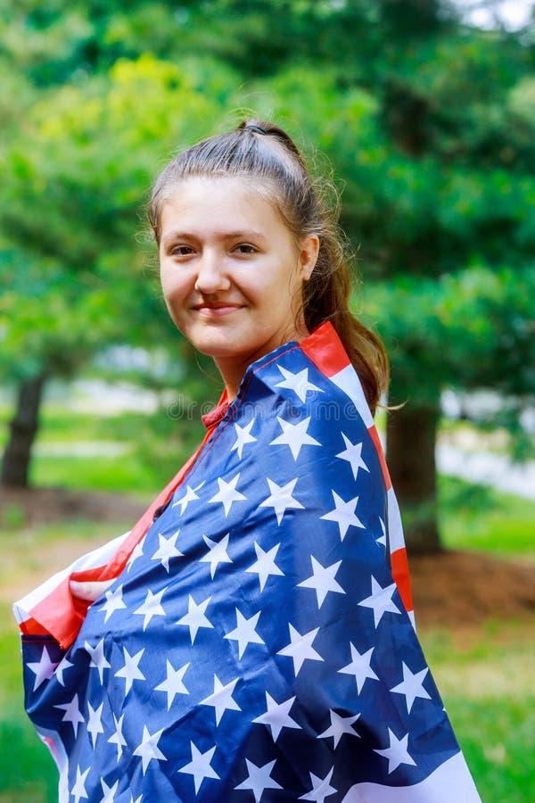 La muchacha se vistió en el patriota americano irreconocible de la bandera de los E.E.U.U., celebración nacional del evento, orgu imagen de archivo libre de regalías