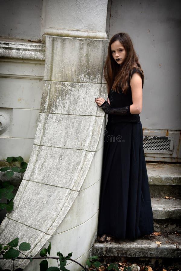 La muchacha se vistió en negro en un cerco fantasmagórico fotografía de archivo