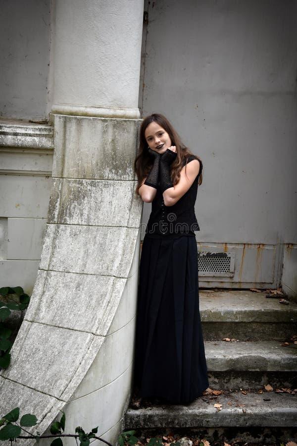 La muchacha se vistió en negro en un cerco fantasmagórico imagenes de archivo