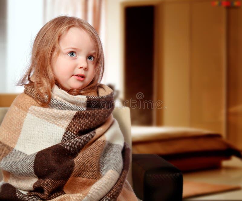 La muchacha se vistió en una manta que se sentaba en el sofá fotografía de archivo