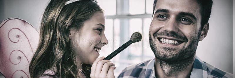 La muchacha se vistió para arriba en un traje de hadas que aplicaba maquillaje en cara de los padres fotos de archivo