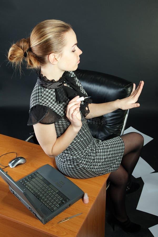 la Muchacha-secretaria está en una oficina fotografía de archivo