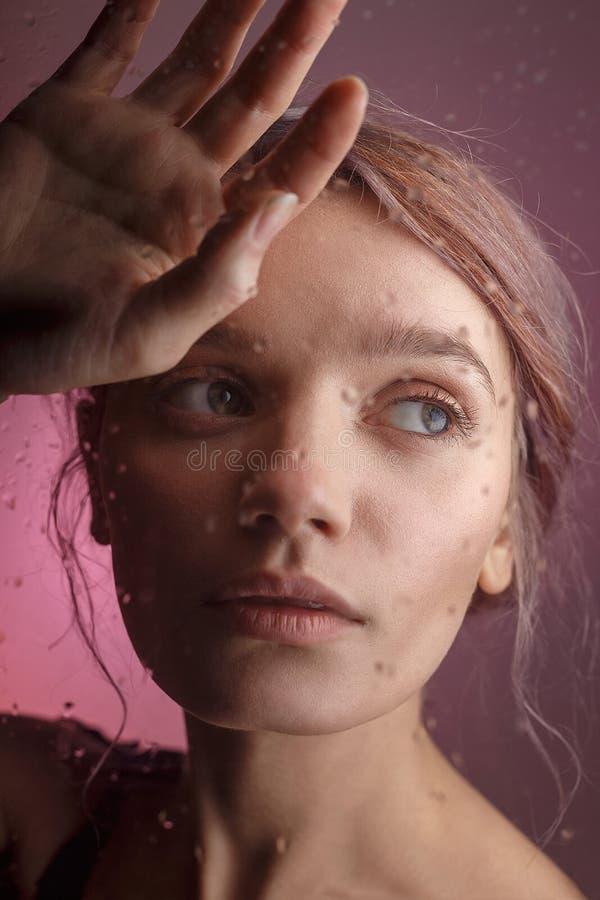 La muchacha sensual joven pone su cara en su mano y se inclina en el vidrio sobre el cual empañó descensos de la corriente abajo  imágenes de archivo libres de regalías