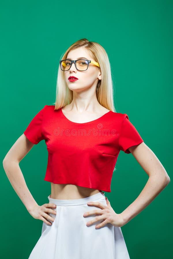 La muchacha seria joven que lleva el top rojo corto y las lentes está presentando en fondo verde Retrato de bastante rubio sensua fotografía de archivo libre de regalías