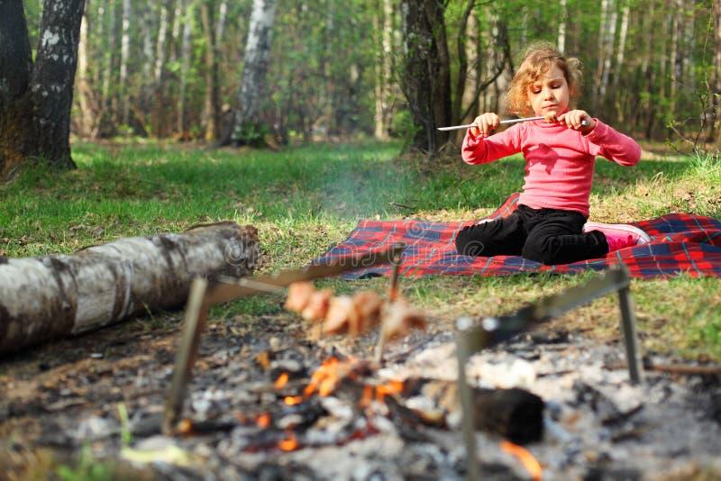 La muchacha sienta y come el kebab asado a la parilla del shish imágenes de archivo libres de regalías