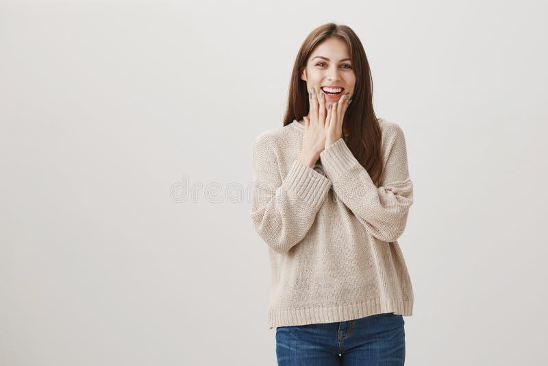 La muchacha siente muy feliz de recibir el regalo lindo Retrato del patrón amistoso atractivo que es sorprendido y emocionado en  foto de archivo