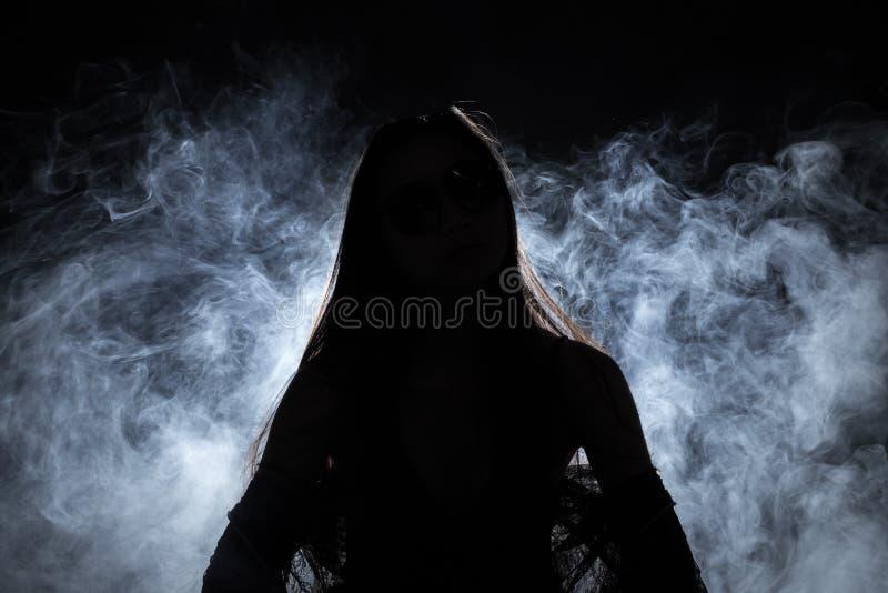 La muchacha sola del corazón quebrado puede llorar, fumar la niebla en fondo oscuro foto de archivo