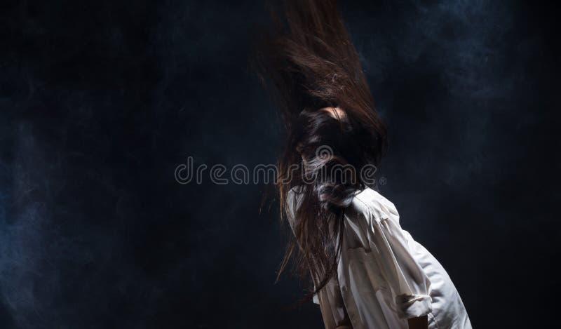 La muchacha sola del corazón quebrado puede llorar, fumar la niebla en fondo oscuro fotos de archivo
