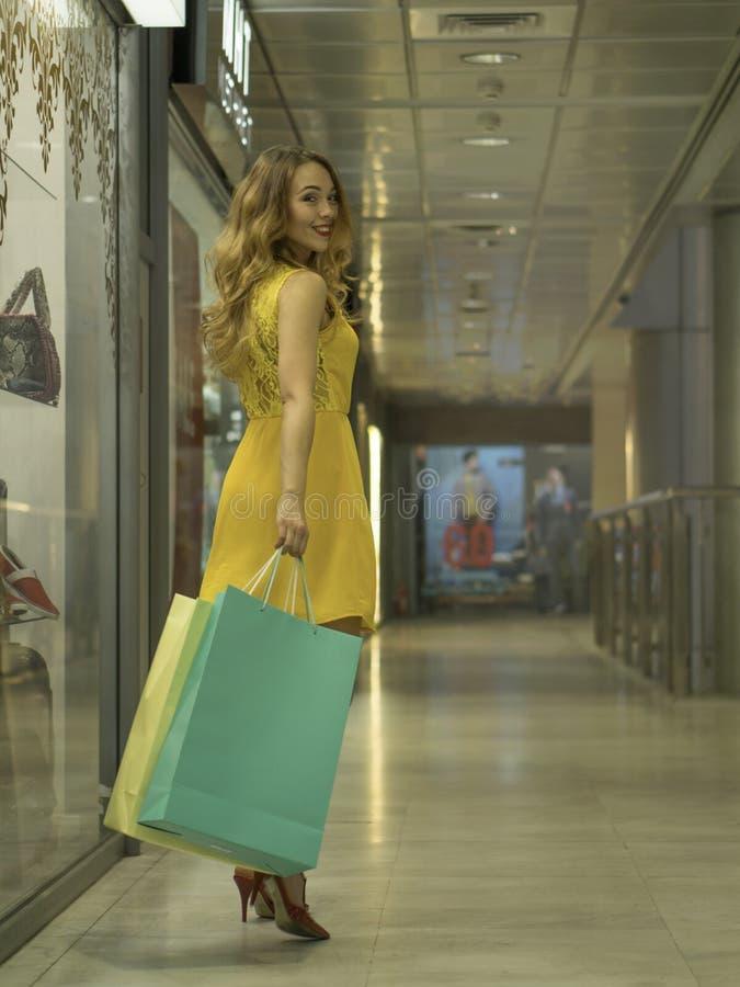 La muchacha sonriente atractiva joven en vestido amarillo está caminando en la alameda con los panieres imagenes de archivo