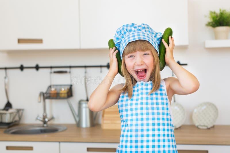 La muchacha sonriente bonita en cocinero viste diversiones con los pepinos fotos de archivo libres de regalías